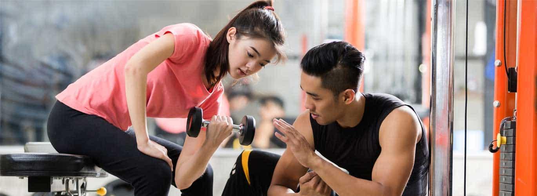 Berufswunsch - Fitnesstrainer - Frau am trainieren mit Support vom Fitnesstrainer