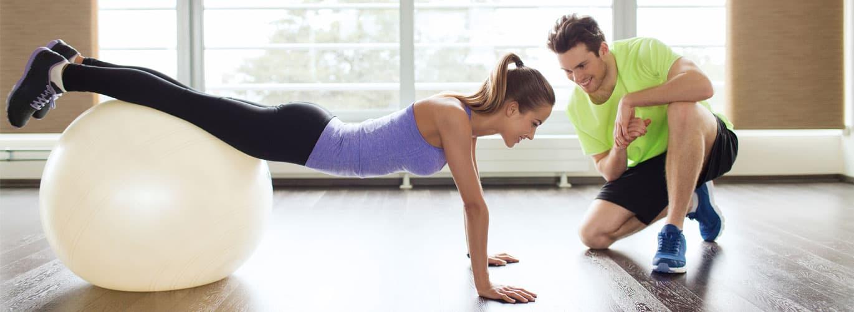 Die Ausbildung zum Reha-Trainer - Frau liegt über einem Gymnastikball
