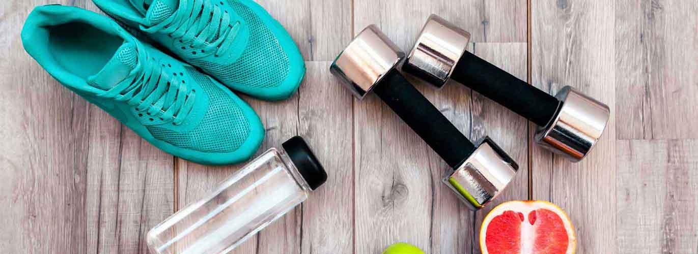 Die B-Lizenz für Fitnesstrainer -Hantel, Sportschuhe und Trinkfalsche liegen auf dem Boden