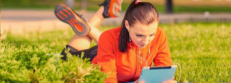 Fitnesstrainer Fernstudium - Frau liegt mit Tablet im Rasen und lernt