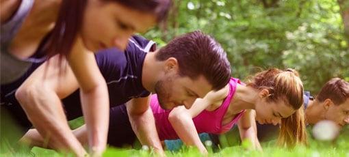 Gruppe macht Fitnessübungen im Park