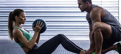 Fitnesstrainer mit Ausbildung hilft Frau beim Training.