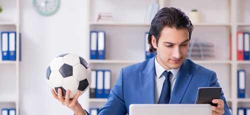 Spielerberater Fussball - Mann hält Ball in der Hand und arbeitet am Laptop